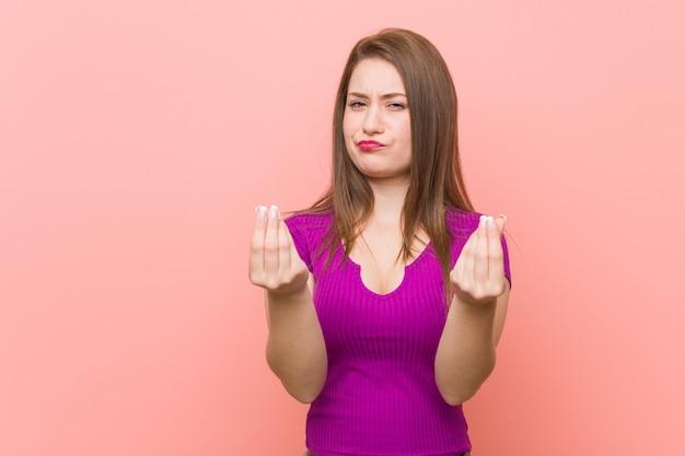 彼女はお金がないことを示すピンクの壁に若いヒスパニック系女性。
