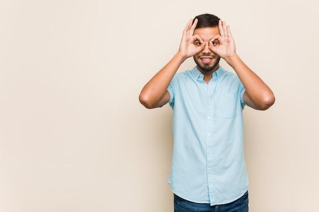 Молодой южно-азиатский мужчина показывает хорошо знаком над глазами