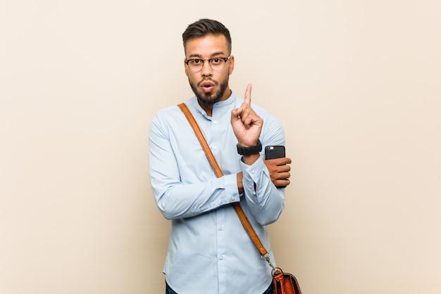 Молодой бизнесмен смешанной гонки азиатский держа телефон имея некоторую отличную идею, концепцию творческих способностей.