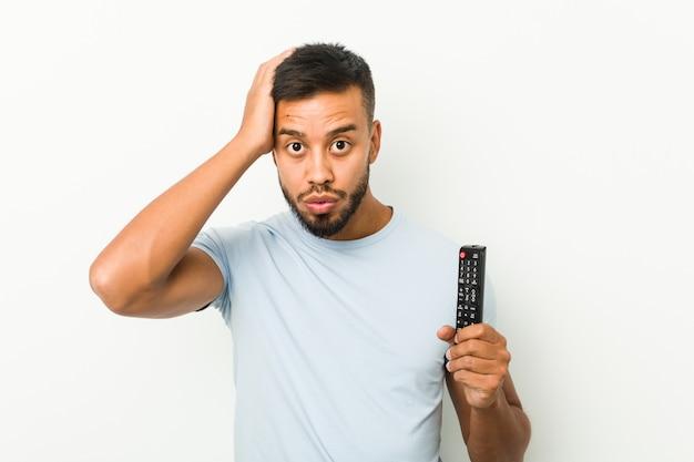 Молодой южноазиатский мужчина, держащий шок от телевизора, вспомнил важную встречу.