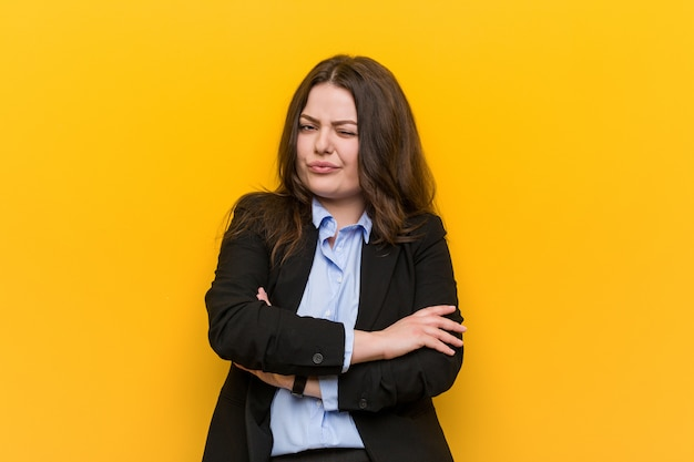不満で顔をしかめ若いプラスのサイズの白人ビジネス女性は、腕を組んでいます。