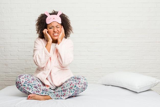 手で耳を覆うピジャマを着てベッドで若いアフリカ系アメリカ人女性。