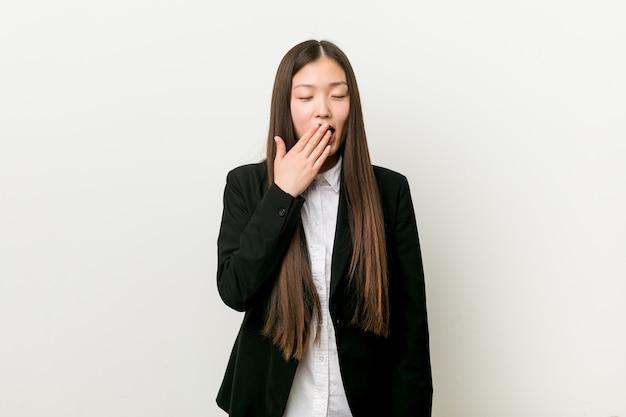 手で口を覆っている疲れたジェスチャーを示すあくび若いかなり中国ビジネス女性。