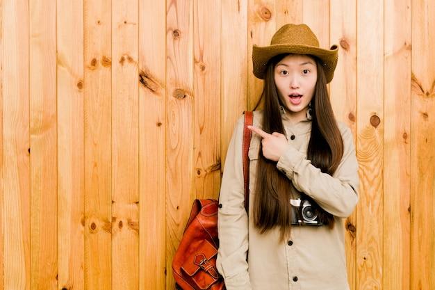 側を指している若い中国人旅行者女性