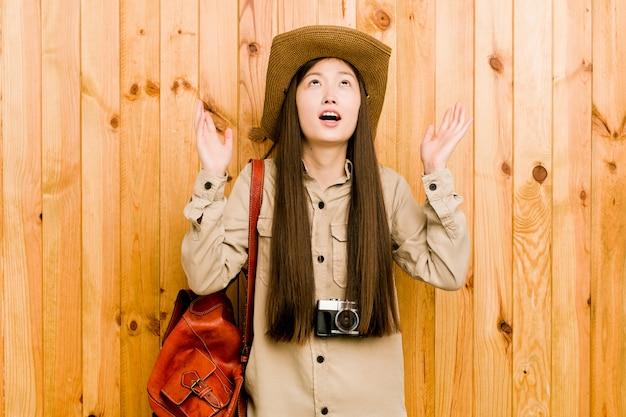 空に叫んで、見上げて、欲求不満の若い中国人旅行者の女性。
