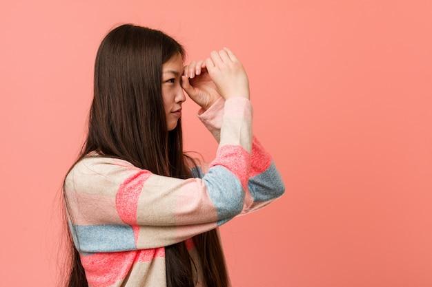 額に手をつけて遠くを見ている若いクールな中国人女性。