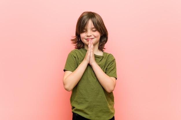 Маленький мальчик, держась за руки в молитве возле рта, чувствует себя уверенно.