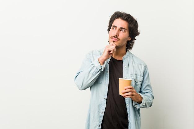 Молодой спокойный человек, пьющий кофе, выглядящий боком с сомнительным и скептическим выражением.