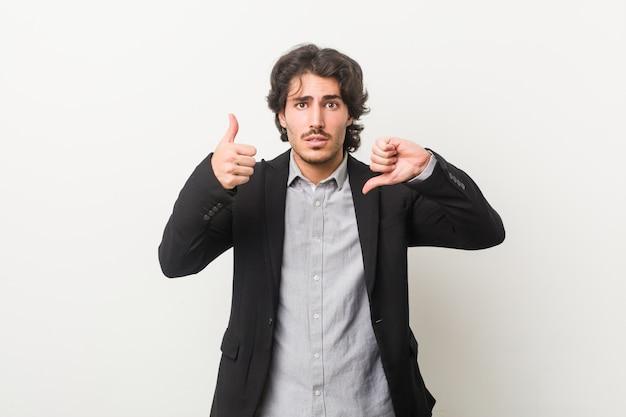 親指と親指を示す白い壁に対して若いビジネスマン、難しい選択コンセプト