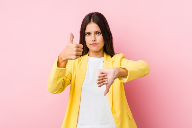 親指と親指を示す若いビジネス女性、難しいコンセプトを選択