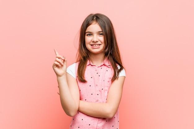 人差し指で元気に指している笑顔かわいい女の子。