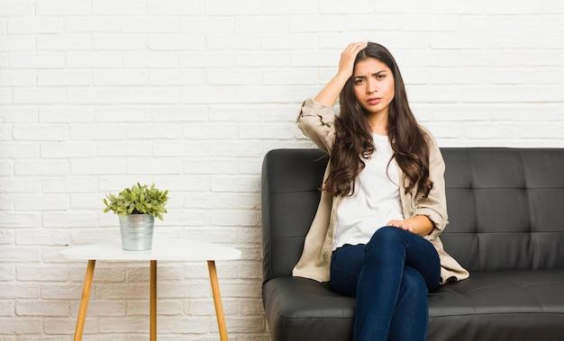 ソファの上に座っている若いアラブ女性は疲れて非常に眠い頭の上に手を維持します。
