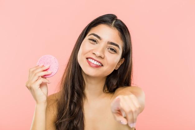 正面を指している顔のスキンケアディスク陽気な笑顔を保持している若いインド人女性。