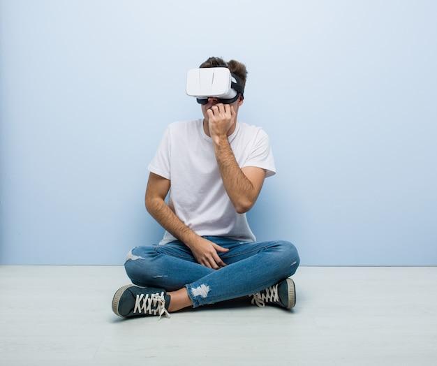 Подросток кавказских человек, используя очки виртуальной реальности, сидя на полу