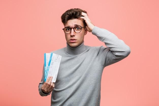 Молодой крутой мужчина держит в руках билеты на самолет в шоке, она вспомнила важную встречу.