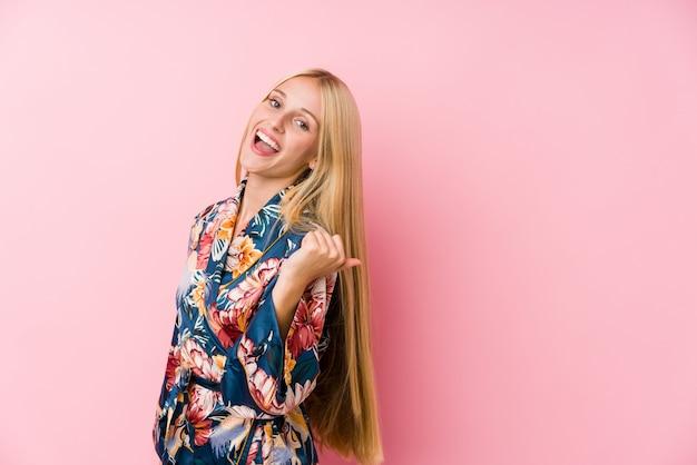 着物のパジャマを着ている若いブロンドの女性は、親指の指で離れて笑って、屈託のないです。
