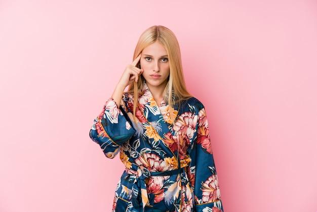 Молодая белокурая женщина нося пижаму кимоно указывая висок с пальцем, думая, сфокусировала на задаче.