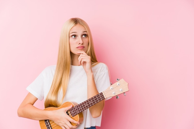 疑わしいと懐疑的な表情で横に見ているウクレレを演奏若いブロンドの女の子。