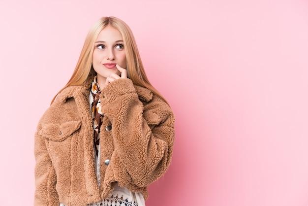 Молодая белокурая женщина нося пальто против розовой стены смотря косой с сомнительным и скептическим выражением.
