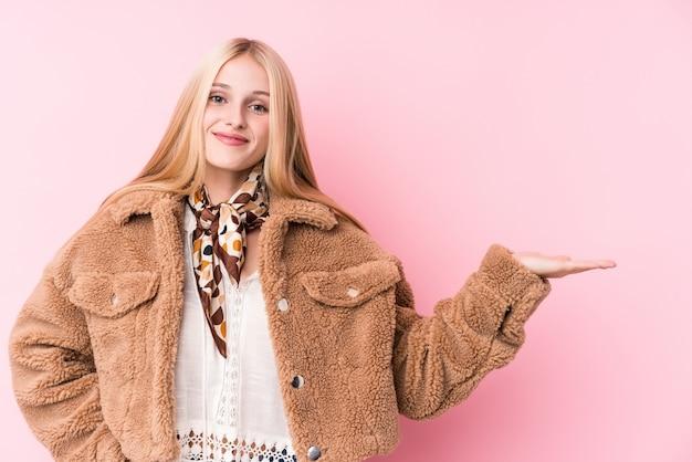 手のひらにコピースペースを示し、腰に別の手を保持しているピンクの壁にコートを着ている若いブロンドの女性。