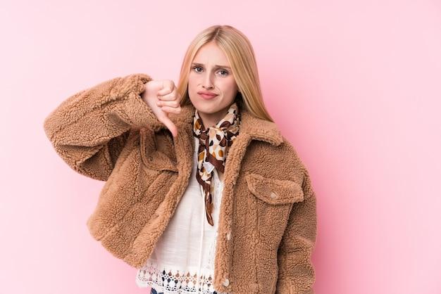 嫌いなジェスチャー、親指ダウンを示すピンクの壁にコートを着ている若いブロンドの女性。不一致の概念。