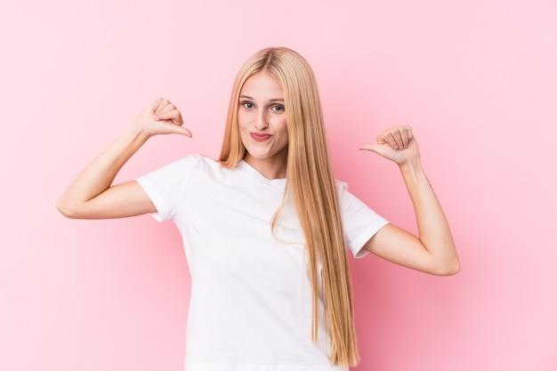 Молодая блондинка на розовой стене чувствует себя гордой и уверенной в себе, пример для подражания.