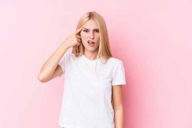 Молодая белокурая женщина на розовой стене показывая жест разочарования с указательным пальцем.
