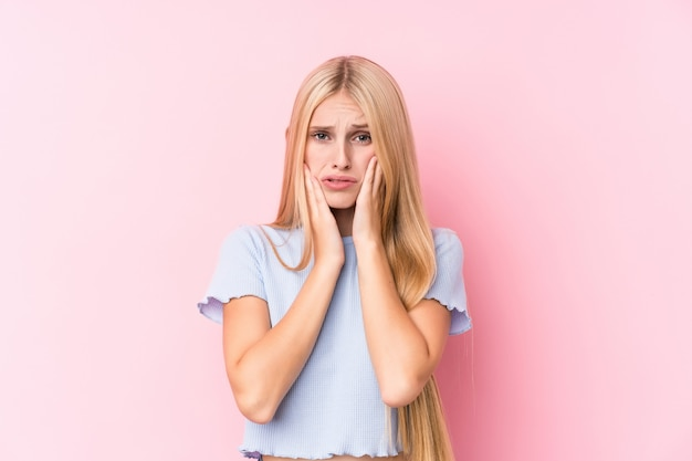 ピンクの壁に泣き言と孤独に泣いている若いブロンドの女性。