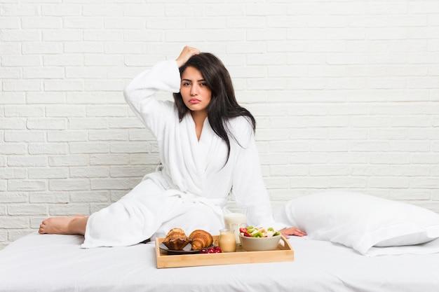 ショックを受けているベッドで朝食を取る若い曲線の女性、彼女は重要な会議を覚えています。
