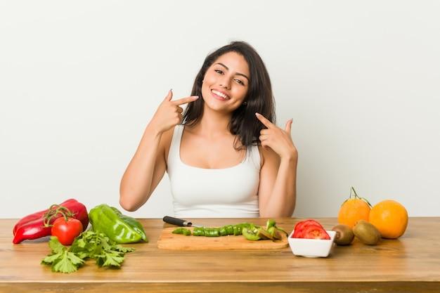健康的な食事を準備する若い曲線の女性の笑顔、口に指を指しています。
