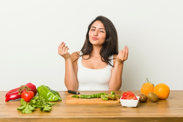 Молодая соблазнительная женщина готовит здоровую еду, показывая, что у нее нет денег.