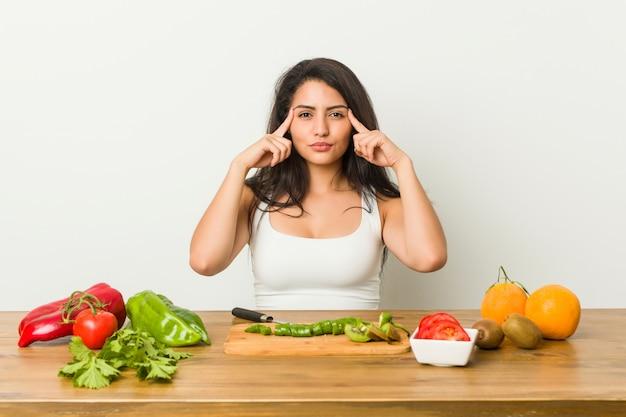 Молодая соблазнительная женщина, готовящаяся здоровая еда, сосредоточилась на задаче, держащей указательные пальцы, указывающие голову