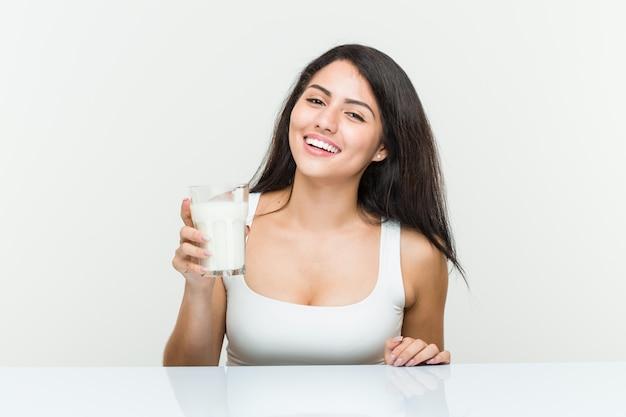 Молодая испанская женщина, держащая стакан молока, счастливый, улыбающийся и веселый.