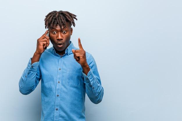 いくつかの素晴らしいアイデア、創造性の概念を持つ携帯電話を保持している若いラスタ黒人男性。