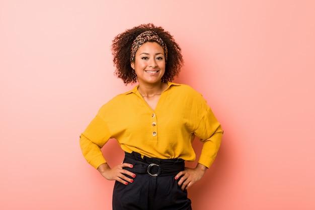 自信を持ってピンクの腰に手を繋いでいる若いアフリカ系アメリカ人女性。