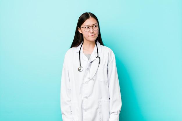 Молодой китайский доктор женщина смущен, чувствует себя сомнительным и неуверенным.