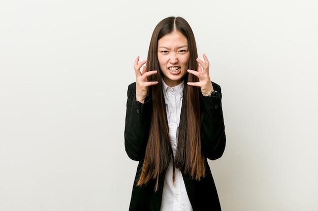 Молодая милая китайская женщина дела расстроенная кричащая с напряженными руками.