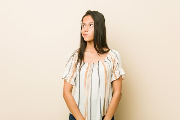 混乱している若いヒスパニック系女性は、疑わしく不安を感じています。