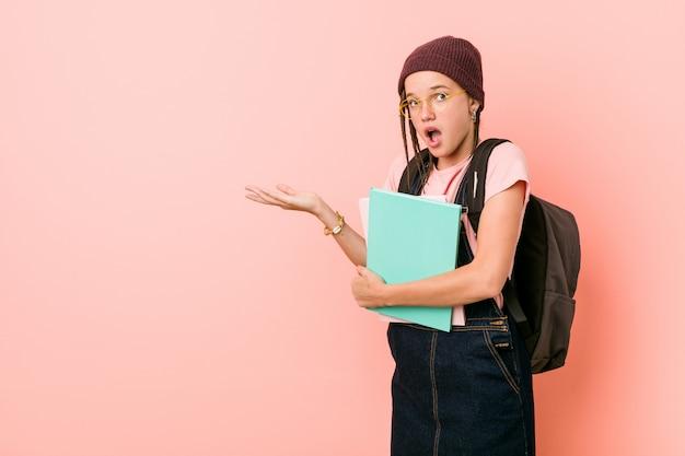 いくつかのノートを保持している若い白人女性は、手のひらにコピースペースを保持して感銘を受けました。