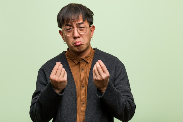 Молодой китайский человек против зеленой стены