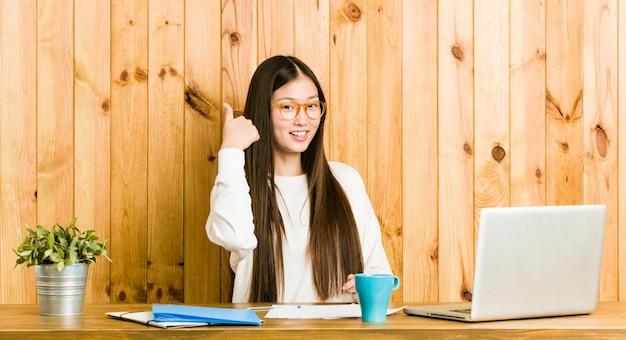 Молодая китайская женщина учится на ее столе указывает пальцем пальцем прочь, смеется и беззаботный.