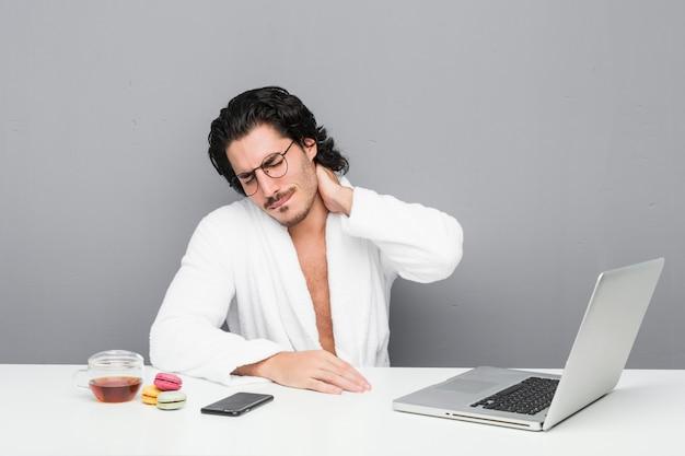 座りがちな生活のために首の痛みに苦しんでいるシャワーの後に働く若いハンサムな男。