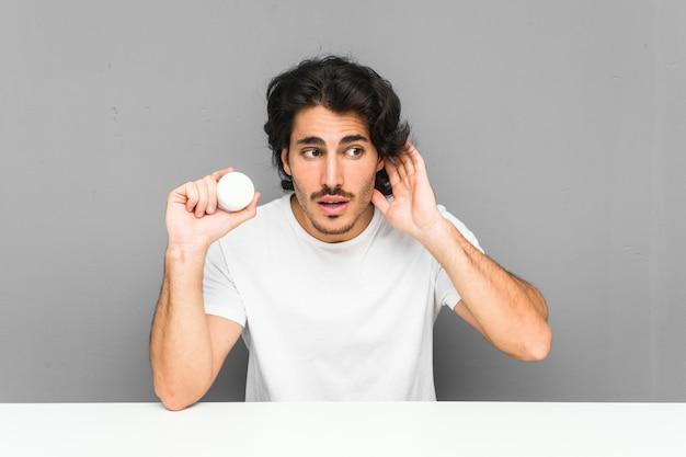 Молодой человек, держащий увлажняющий крем, пытается слушать сплетни.