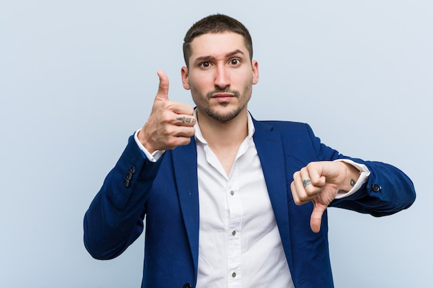 親指と親指を示す若いビジネス白人男性、難しいコンセプトを選択