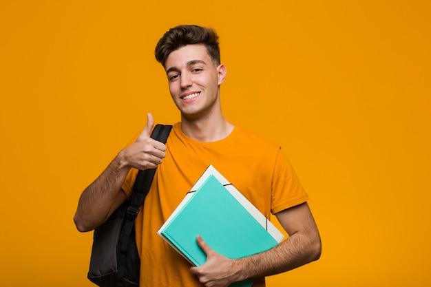 勝利のサインを示し、広く笑顔の本を保持している若い学生男。