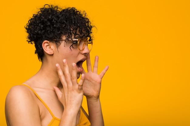 Молодая женщина афроамериканцев с кожей знак рождения кричит громко, держит глаза открытыми и руки напряженными.