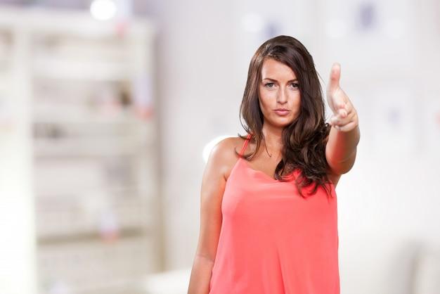 銃のジェスチャーをしている若い女性