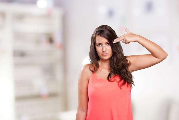 自殺ジェスチャーをしている若い女性