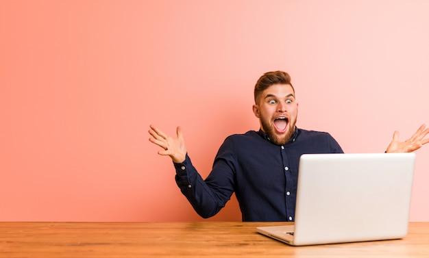 Молодой человек, работающий с его ноутбуком, празднует победу или успех