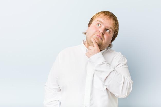 疑わしいと懐疑的な表情で横に探している若い本物の赤毛のデブ男。